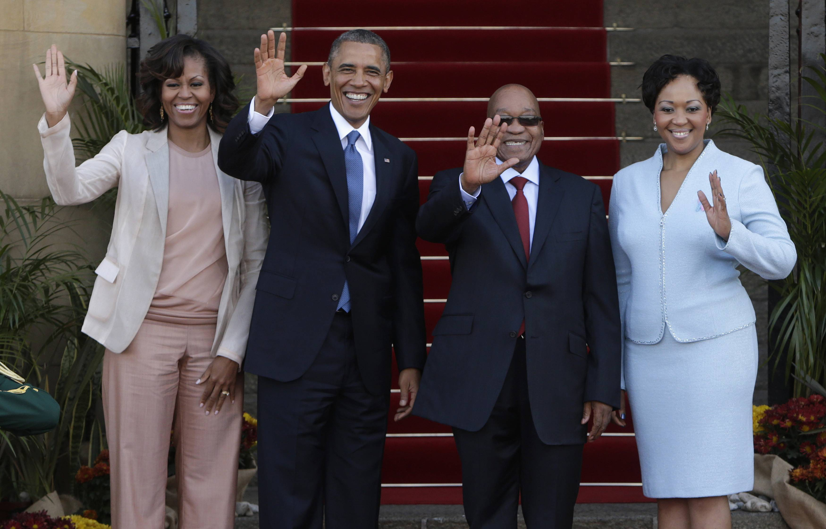 U.S. President Barack Obama (2nd L) and First Lady Michelle Obama (L) wave next to South Africa's President Jacob Zuma (2nd R) and his wife, First Lady Thobeka Madiba-Zuma, at the Union Building in Pretoria, June 29, 2013. Obama paid tribute to anti-apartheid hero Nelson Mandela as he flew to South Africa on Friday but played down expectations of a meeting with the ailing black leader during an Africa tour promoting democracy and food security. REUTERS/Gary Cameron   (SOUTH AFRICA - Tags: POLITICS)